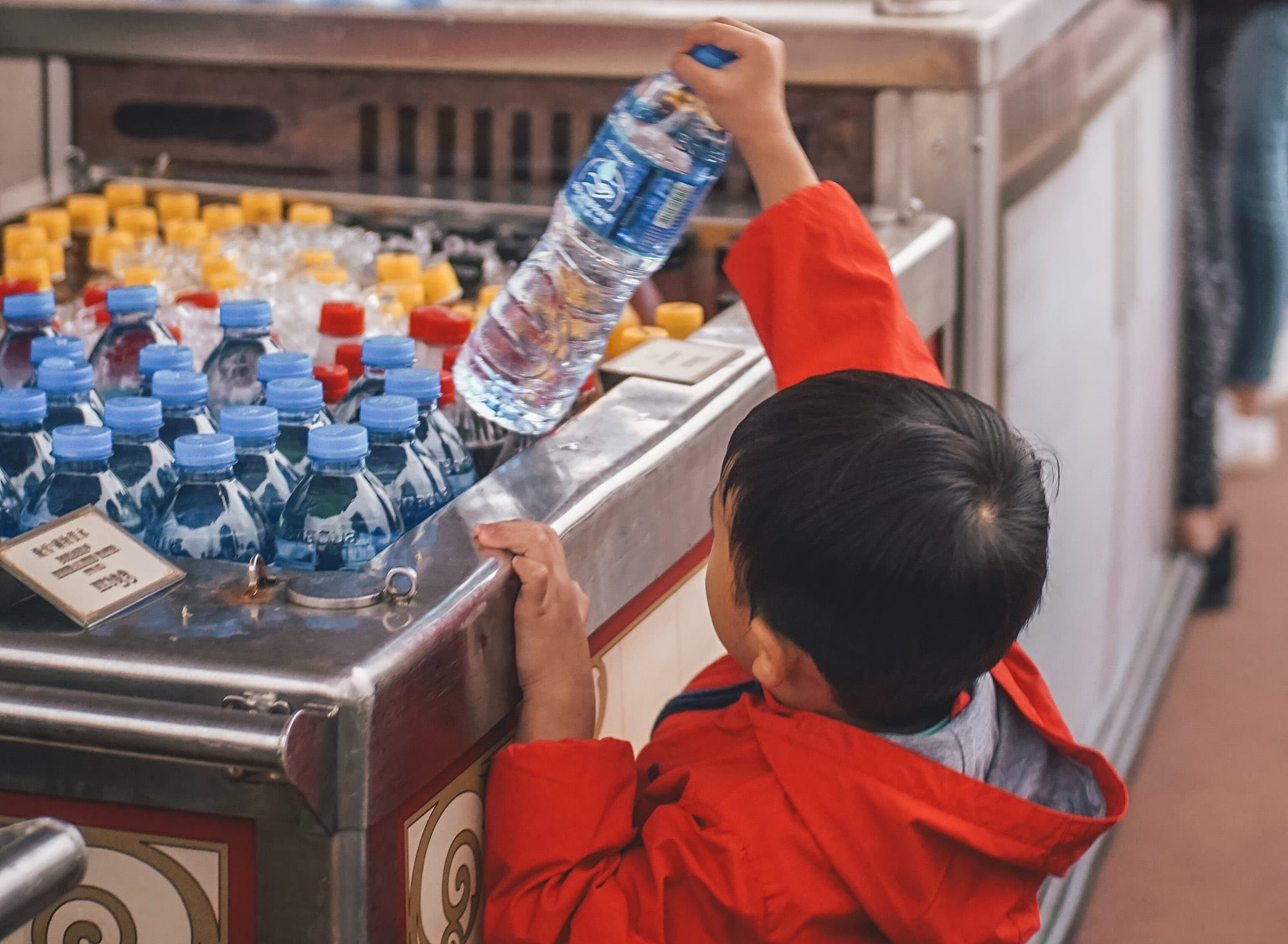 Young boy pickup a bottle of water. REVOLVE